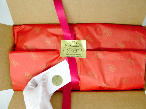 shipping box packaging with gift card ribbon stickers and red tissue paper